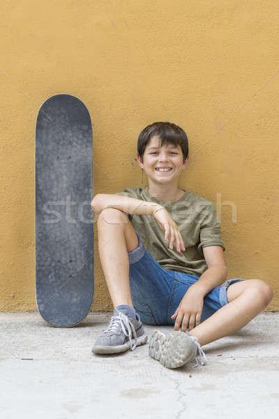 Sorridente menino andar de skate sessão sozinho piso Foto stock © 2Design