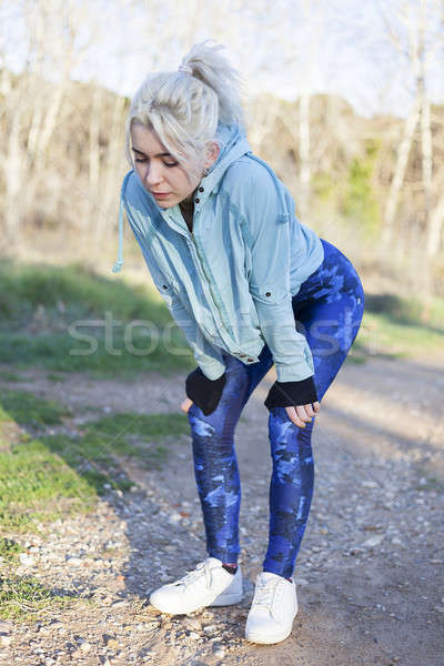 Active cheerful blonde pausing after a run in a park on a sunny  Stock photo © 2Design