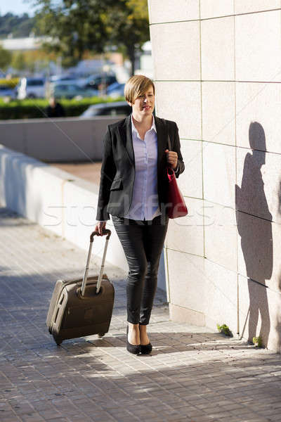 Businesswoman with trolley bag walking in urban environment Stock photo © 2Design