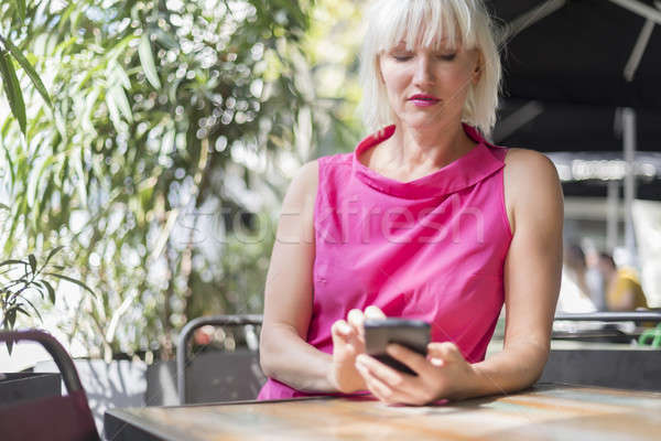 Stock photo: Mature blonde hair woman using a mobile phone outdoors