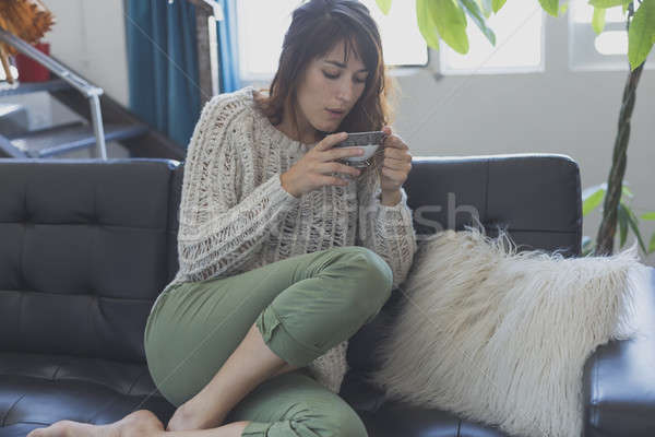 A woman sitting  on the couch, while looking forward and smiling Stock photo © 2Design