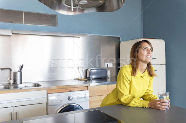 Portrait of a woman contemplating at the kitchen holding a glass Stock photo © 2Design
