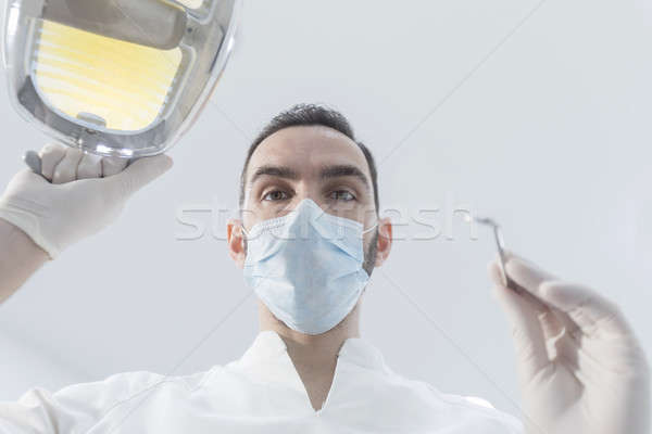 Dentist wearing surgical mask while holding angled mirror and dr Stock photo © 2Design