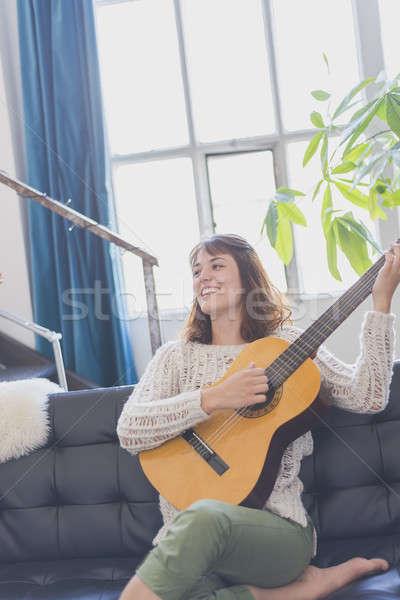 Mooie jonge vrouw vergadering sofa spelen gitaar Stockfoto © 2Design