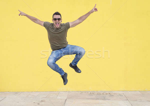 Genç güneş gözlüğü atlama sarı duvar kot Stok fotoğraf © 2Design