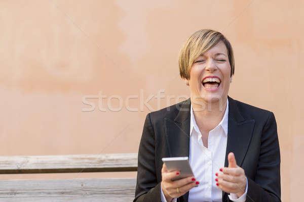 Mulher de negócios sorridente telefone móvel mão sessão banco Foto stock © 2Design