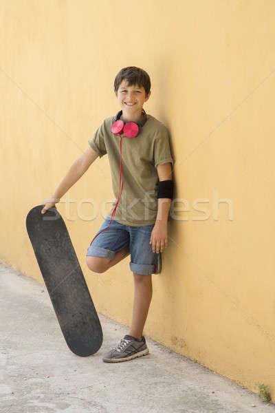 Genç kaykay şehir sokak kulaklık etrafında boyun Stok fotoğraf © 2Design