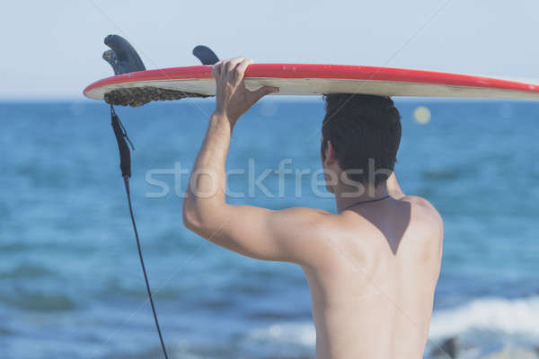 handsome surfer holding surfboard on head from rear Stock photo © 2Design