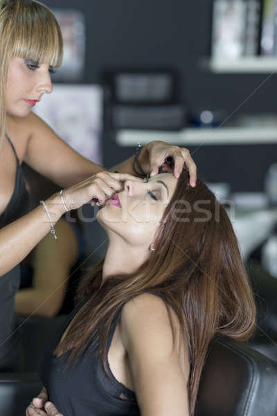 Young makeup artist doing makeover to pretty model Stock photo © 2Design