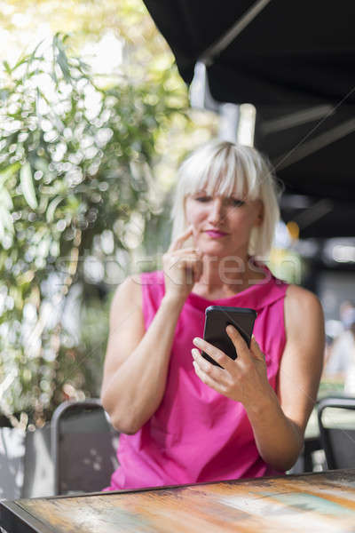 Mature blonde hair woman using a mobile phone outdoors Stock photo © 2Design