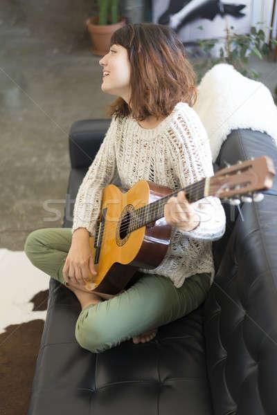 ストックフォト: 美しい · 若い女性 · 座って · ソファ · 演奏 · ギター