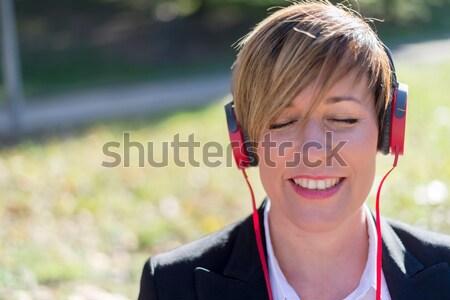 Menina ouvir música fones de ouvido parque empresária mulher Foto stock © 2Design