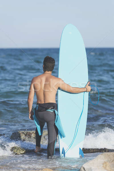 Young attractive surfer holding his surfboard at the beach Stock photo © 2Design