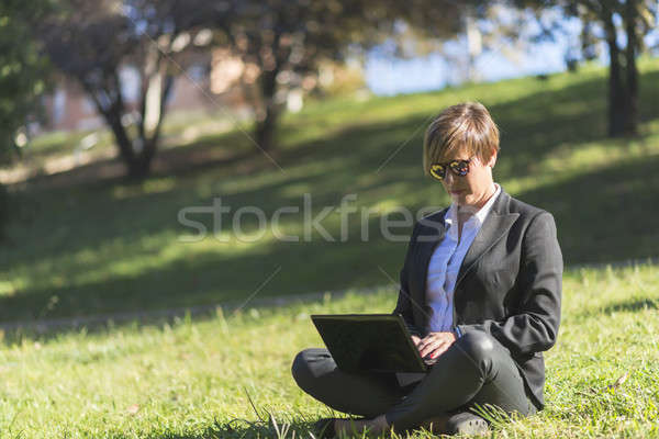 A businesswoman Sitting In Field Using Laptop Stock photo © 2Design