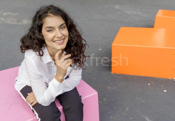 Gülümseyen kadın bakıyor kamera oturma açık havada siyah saçlı Stok fotoğraf © 2Design