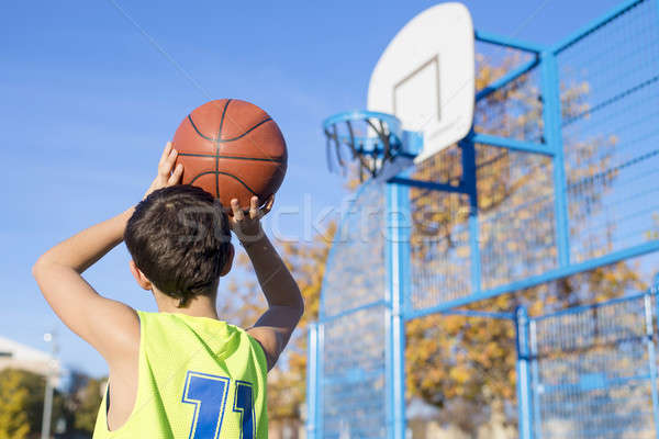 teenager throwing a basketball into the hoop from behind Stock photo © 2Design