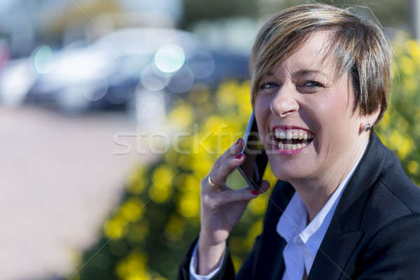 Executive talking on phone looking at camera on the street Stock photo © 2Design