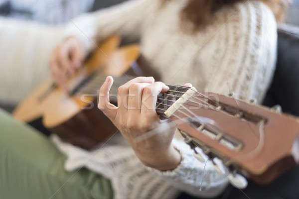Belo mulher jovem sessão sofá jogar guitarra Foto stock © 2Design