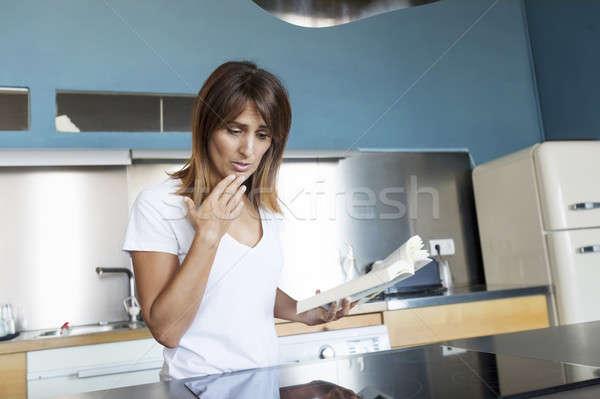 Retrato sorridente mulher jovem leitura livro cozinha Foto stock © 2Design