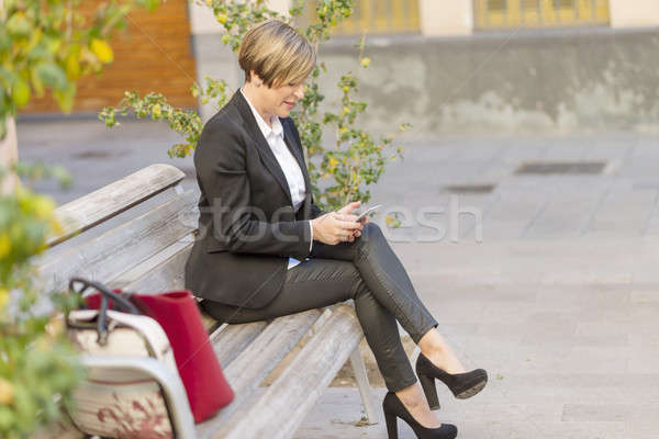 Femme d'affaires smartphone séance ville parc banc Photo stock © 2Design