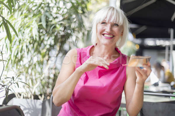 Beautiful blonde woman making up using a silver  mirror - Outdoo Stock photo © 2Design
