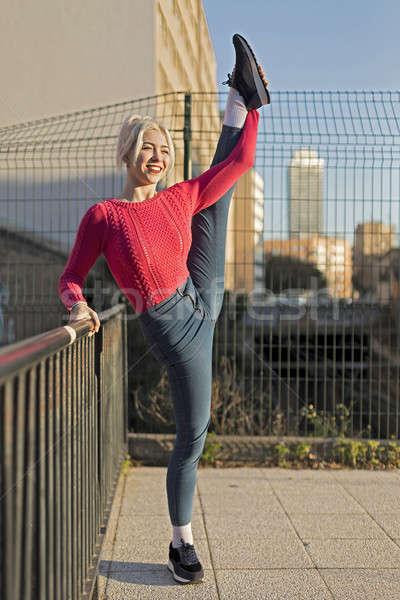 Beautiful smiling woman lifting her leg on the street Stock photo © 2Design