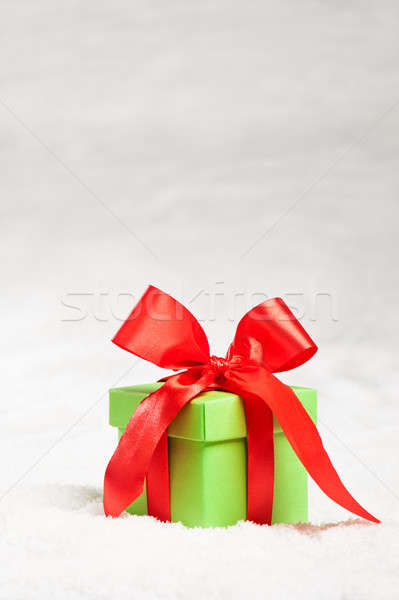 Green present with red ribbon over snow Stock photo © 3523studio