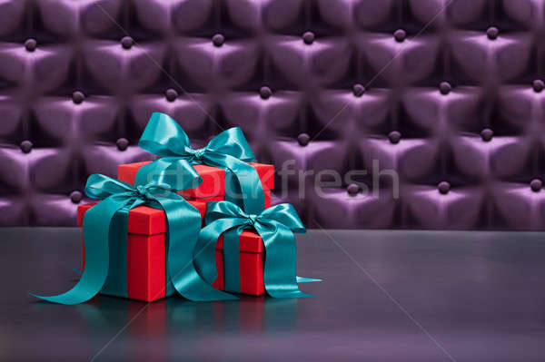 Red present in front of a button tufted background Stock photo © 3523studio