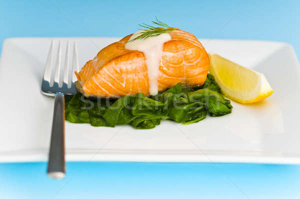 Salmon steak on spinach, decorated with lemon and sauce Stock photo © 3523studio