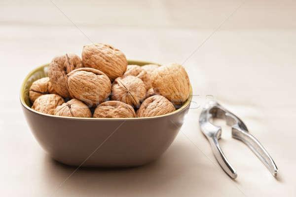Walnut in a bowl with nutcracker Stock photo © 3523studio