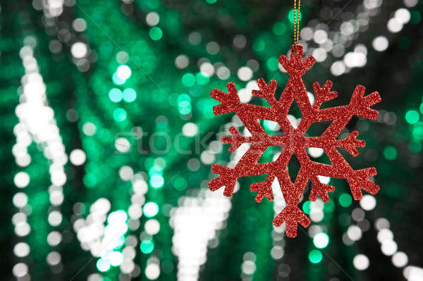 Red snow flake on a green, silver glitter background Stock photo © 3523studio