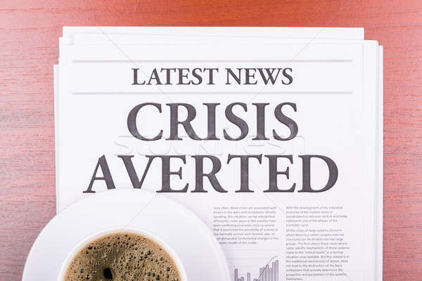 Stock photo: The newspaper CRISIS AVERTED  and coffee