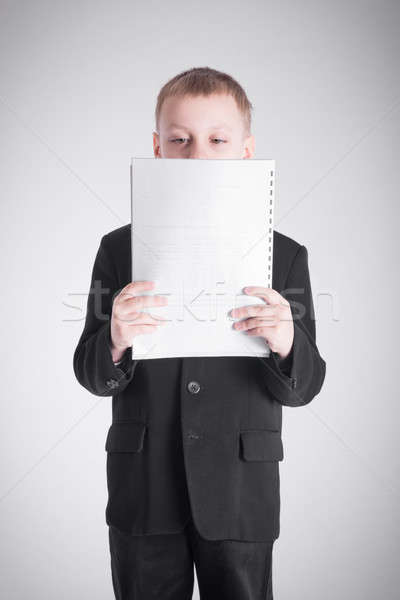 Boy looking at a stack of paper Stock photo © a2bb5s