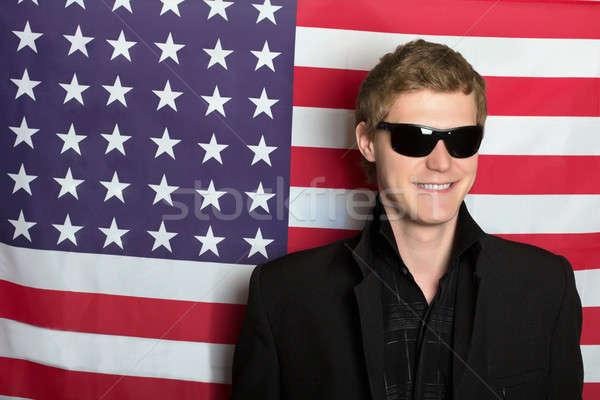 Uśmiechnięty młody człowiek okulary amerykańską flagę człowiek szczęśliwy Zdjęcia stock © acidgrey