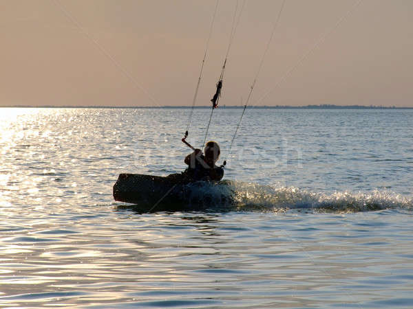 Stock photo: Silhouettes kitesurf on a gulf on a sunset 2