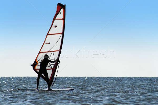 Silhouette of a windsurfer on the blue sea Stock photo © acidgrey
