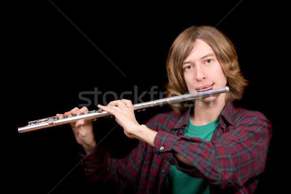 The young man plays a flute over black Stock photo © acidgrey