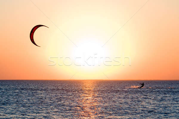 Stock photo: Kitesurfer on a gulf on a sunset