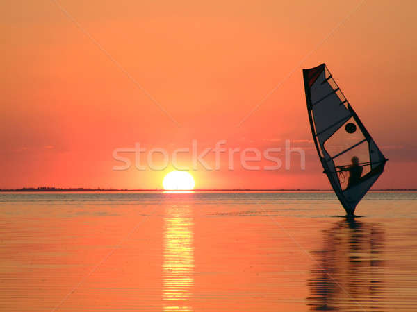 Silhouette of a windsurfer on waves of a gulf on a sunset 3 Stock photo © acidgrey