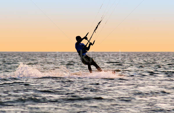 Silhouette of a kitesurfer on waves of a gulf  Stock photo © acidgrey