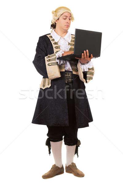 Különc fiatalember középkori jelmez pózol laptop Stock fotó © acidgrey