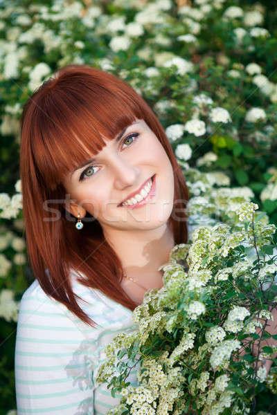 Glimlachende vrouw poseren bloei bush vrouw meisje Stockfoto © acidgrey