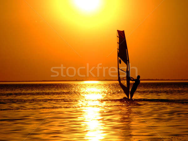 Silhouette of a windsurfer on waves of a gulf on a sunset Stock photo © acidgrey