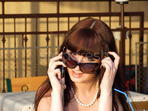 A smiling girl in sunglasses talks by a mobile phone2 Stock photo © acidgrey