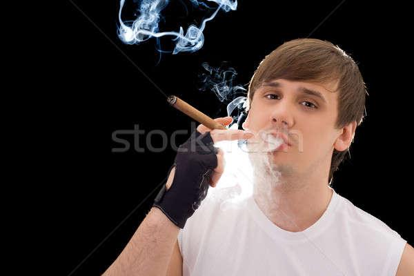 Joven fumar cigarro aislado negro humo Foto stock © acidgrey