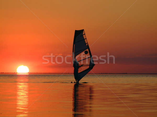 Stock photo: Silhouette of a windsurfer on waves of a gulf on a sunset 2