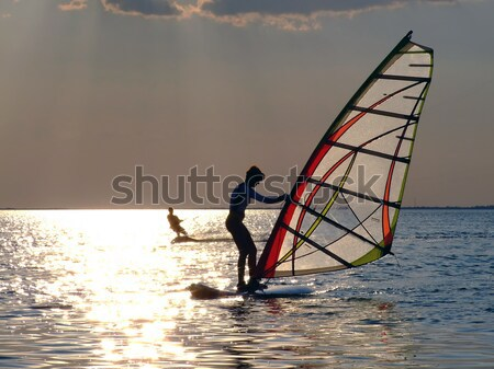 A women is learning windsurfing at the sunset Stock photo © acidgrey