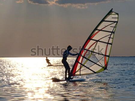 Nők tanul windszörf naplemente tengerpart fény Stock fotó © acidgrey