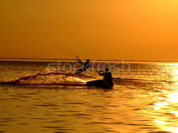 Silhouette of a two kitesurf on a gulf on a sunset Stock photo © acidgrey