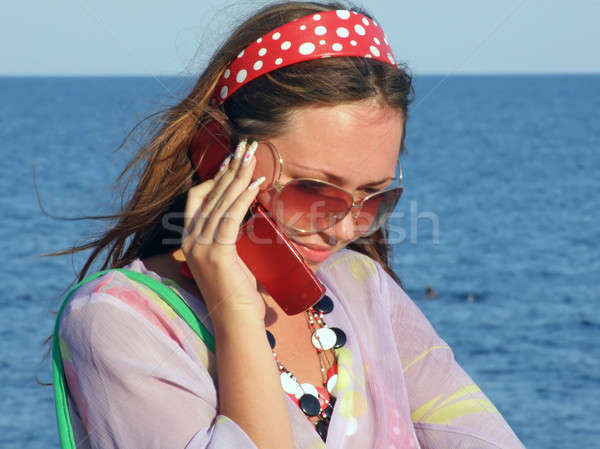 The beautiful girl talks by a mobile phone on the sea Stock photo © acidgrey